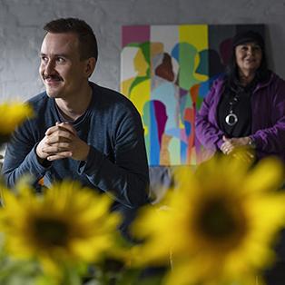 Mies istuu ja hymyilee. Nainen seisoo miehen takana. Edessä auringonkukkia.