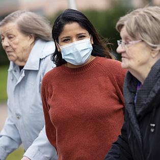 Hoitaja kävelee ulkona kahden vanhan naisen kanssa.