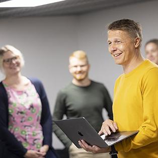 Mies hymyilee tietokone kädessään