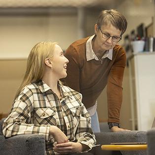 Kaksi naista keskustelevat toimistossa.