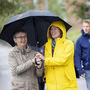 Kaksi naista nauravat sateenvarjon alla.